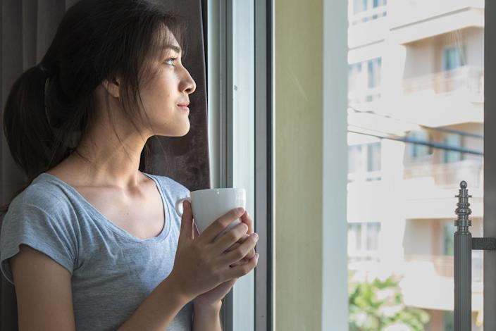 woman standing staring out window