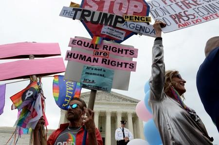 LGBTQ activists and supporters hold rally on the steps of the Supreme Court as it hears major LGBT rights case in Washington
