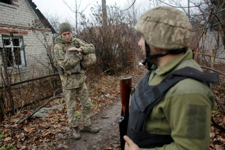 Pondering with concern what concessions to Russia might be forced from their side in summit talks, Ukrainian servicemen patrol near the town of Avdiivka on the frontline with Russia-backed separatists