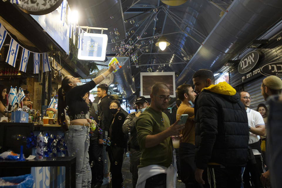 A bartender uses a bubble gun during Independence Day celebrations at the Mahane Yehuda Market in Jerusalem, after more than a year of coronavirus restrictions, Wednesday, April 14, 2021. (AP Photo/Maya Alleruzzo)