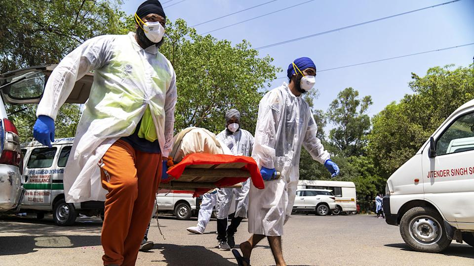Voluntary health workers, pictured here carrying the body of a deceased Covid-19 patient.