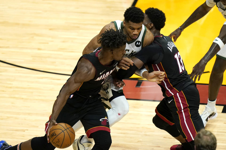 Miami Heat forward Jimmy Butler, left, drives to the basket as center Bam Adebayo (13) applies a pick against Milwaukee Bucks forward Giannis Antetokounmpo, center, during the first half of Game 4 of an NBA basketball first-round playoff series, Saturday, May 29, 2021, in Miami. (AP Photo/Lynne Sladky)