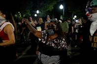 People hold signs during a third night of demonstrations against the shooting of Jacob Blake in Kenosha, Wisconsin on August 25, 2020