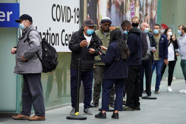 People queue to receive a Covid-19 jab at the pop-up vaccination centre at Westfield Stratford City shopping centre