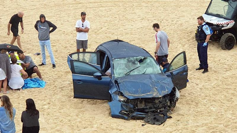 Rescue workers at the scene of a car crash on Maroubra beach.