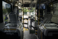 A protective plastic cover is installed in a shuttle bus to help curb the spread of COVID-19 prior to the 2020 Summer Olympics Sunday, July 11, 2021, in Tokyo. (AP Photo/Jae C. Hong)