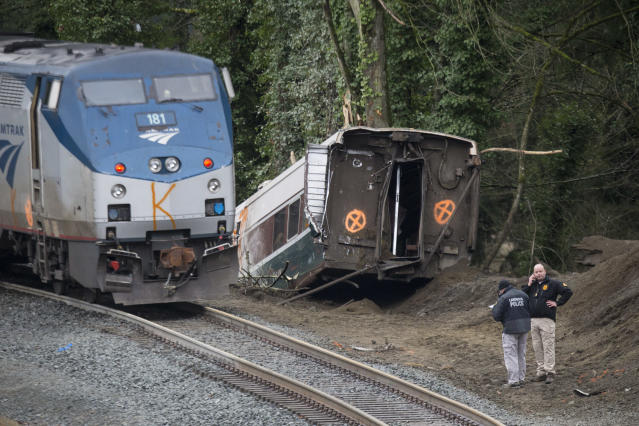 <p>Law enforcement work at the scene of a Amtrak train derailment on December 18, 2017, 2017 in DuPont, Washington. The derailment also closed southbound I-5. (Photo: Stephen Brashear/Getty Images) </p>