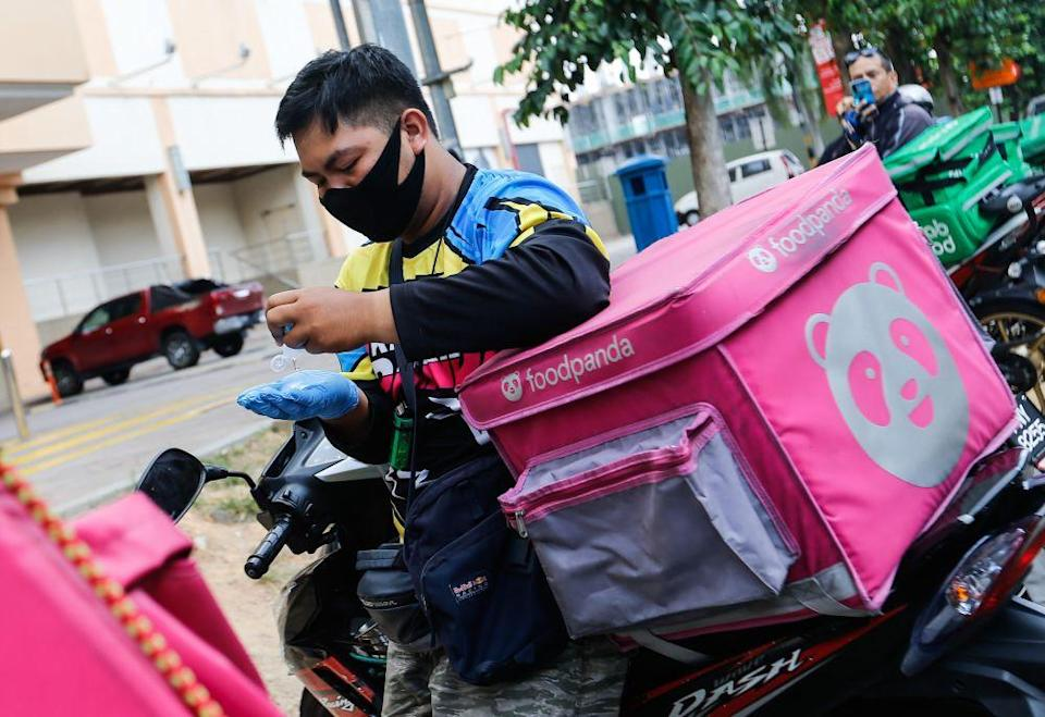 A Foodpanda rider is pictured sanitising his hands before making a delivery in George Town March 24, 2020. — File picture by Sayuti Zainudin