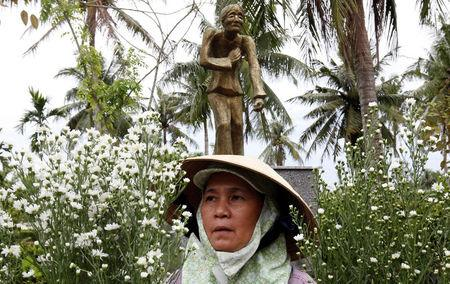 A woman arranges flower in front of a statue in a museum during the 50th anniversary of the My Lai massacre in My Lai village, Vietnam March 15, 2018. REUTERS/Kham