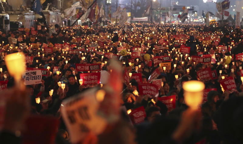 FILE - In this Nov. 19, 2016, file photo, South Korean protesters hold up candles during a rally calling for South Korean President Park Geun-hye to step down in Seoul, South Korea. South Korean President Moon Jae-in's office said Tuesday, July 10, 2018, that Moon has ordered an investigation into an allegation that the military drew up a plan to mobilize troops if protests worsened over the fate of his impeached predecessor last year. (AP Photo/Lee Jin-man, File)