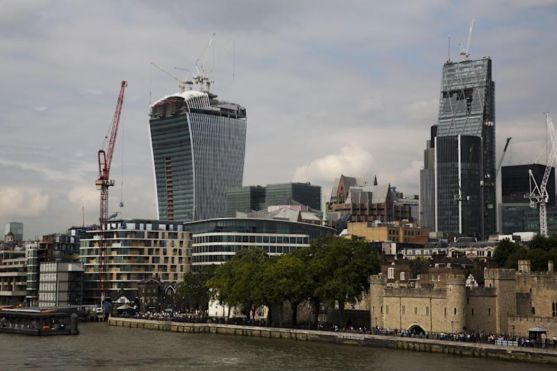 """The 37-storey skyscraper at 20 Fenchurch Street, top left, which is still under construction is seen near part of the Tower of London, bottom right, in the City of London, Tuesday, Sept. 3, 2013. Developers for an unfinished skyscraper in central London say they are investigating the way the building reflects bright sunlight _ after claims that the intense glare melted parts of a car parked nearby. The companies behind the skyscraper, nicknamed the """"Walkie-Talkie"""" because of its curved shape, are responding to complaints from the owner of a Jaguar who told the BBC that the mirror, panels and the Jaguar badge had all melted from the concentrated heat of sunlight reflected from the building. (AP Photo/Matt Dunham)"""