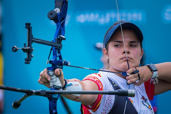 female archer pulls back the bowstring