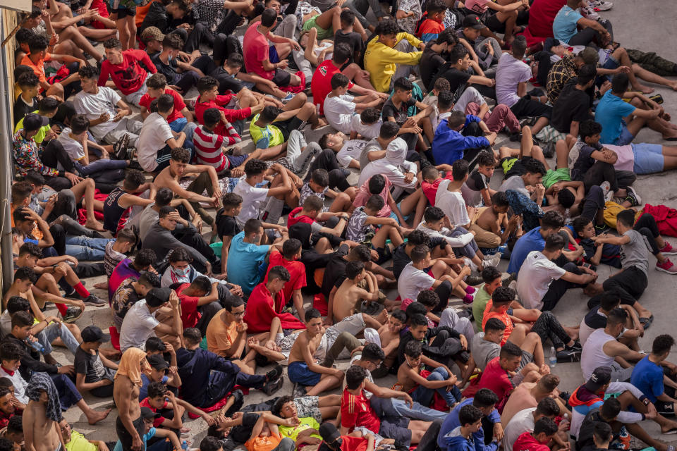 Unaccompanied minors who crossed into Spain are gathered outside a warehouse used as temporary shelter as they wait to be tested for COVID-19 at the Spanish enclave of Ceuta, near the border of Morocco and Spain, Wednesday, May 19, 2021. Social services for the small city perched on an outcropping in the Mediterranean buckled under the strain after more than 8,000 people crossed into Spanish territory during the previous two days. (AP Photo/Bernat Armangue)