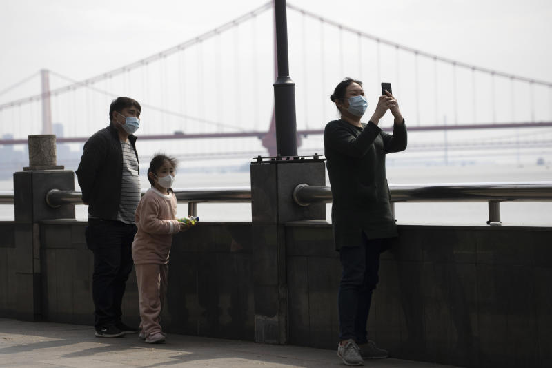 Residents walk along the banks of the Yangtze River in Wuhan in central China's Wuhan province on Wednesday, April 1, 2020. Skepticism about China's reported coronavirus cases and deaths has swirled throughout the crisis, fueled by official efforts to quash bad news in the early days and a general distrust of the government. In any country, getting a complete picture of the infections amid the fog of war is virtually impossible. (AP Photo/Ng Han Guan)