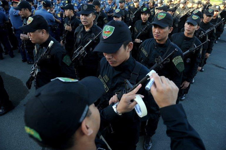 Philippine police seal the muzzles of their guns with tape in Manila on December 29, 2012 to prevent stray gunfire