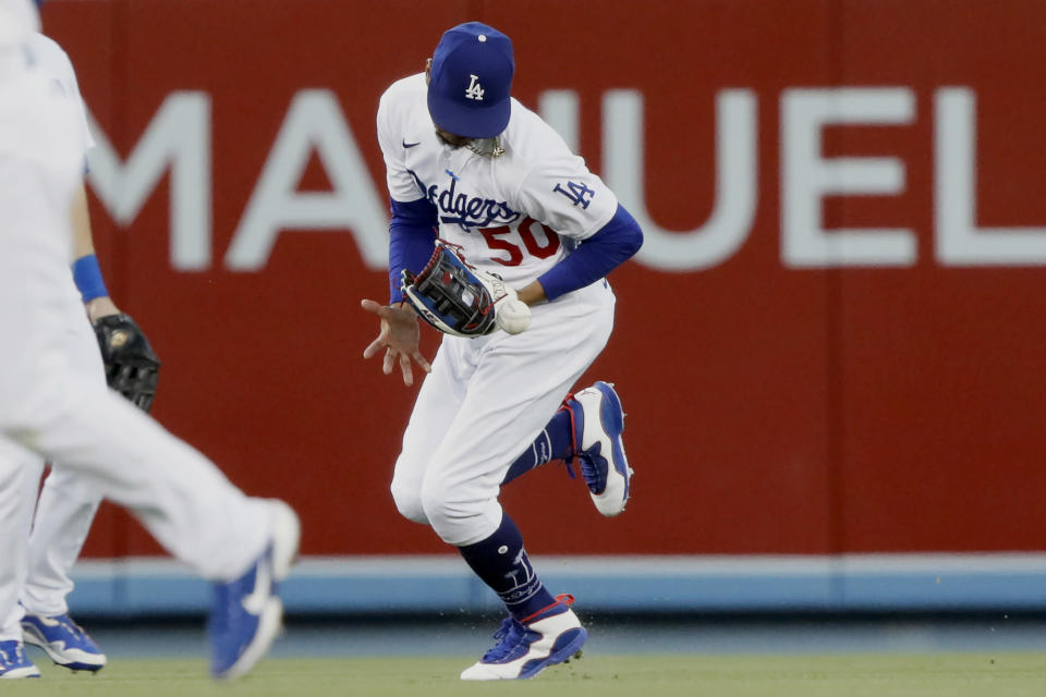 Los Angeles Dodgers center fielder Mookie Betts drops a fly ball hit by Texas Rangers' Isiah Kiner-Falefa for an error during the third inning of a baseball game in Los Angeles on Saturday, June 12, 2021. (AP Photo/Alex Gallardo)