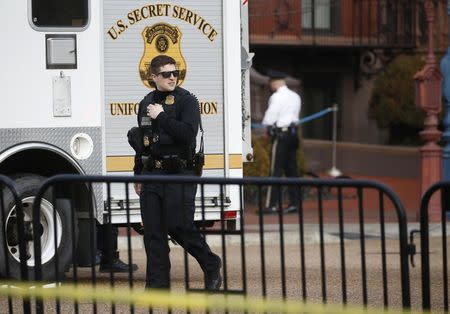 Law enforcement officials gather on Pennsylvania Avenue after reports of a suspicious vehicle near the White House in Washington