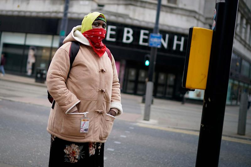 A woman wearing a scarf for protection walks through Manchester City centre: Getty Images