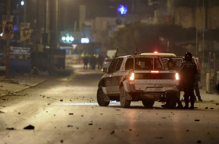 Tunisian police block a road in the working-class district of Ettadhamen on the edge of Tunis amid clashes with protesters on January 17, 2021