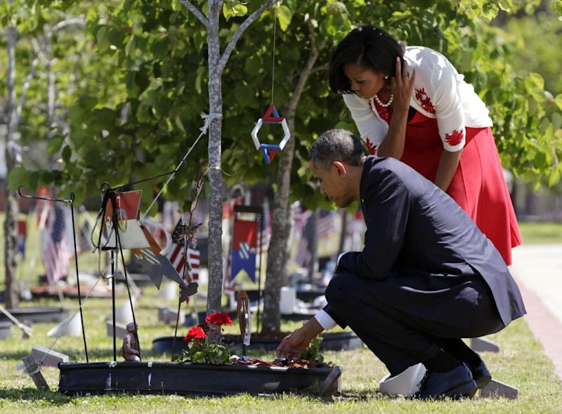 President Barack Obama and first lady Michelle Obama place a flag and a coin on a marker as they visit Warriors Walk at Fort Stewart, Ga., Friday, April 27, 2012, before speaking to troops, veterans and military families at the Third Infantry Division Headquarters. Warriors Walk pays tribute to the 441 fallen service members who have died in Operations Iraqi and Enduring Freedom and Operation New Dawn while assigned or attached to the 3rd Infantry Division or Fort Stewart and Hunter Army Airfield. Each fallen service member is honored with a plaque and an Eastern Redbud tree. (AP Photo/Carolyn Kaster)