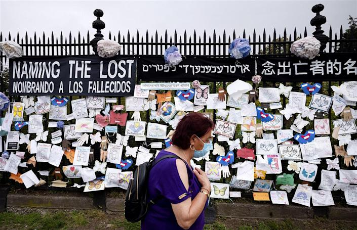 A woman passes a fence outside Green-Wood Cemetery, adorned with tributes to victims of Covid-19, in Brooklyn, N.Y., on May 28. The memorial is part of the Naming the Lost project, which seeks to humanize victims who are often simply listed as statistics.