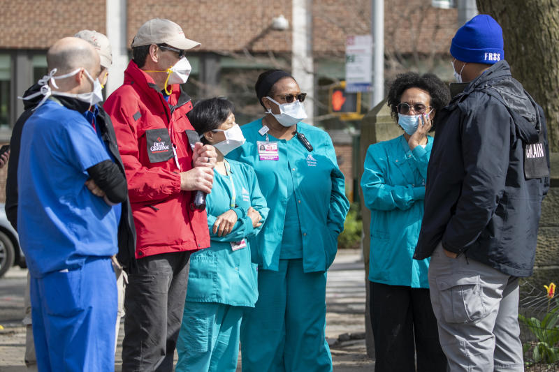 Medical personnel talk to chaplains, left, as they tour the Samaritan's Purse 68 bed emergency field hospital especially equipped with a respiratory unit in New York's Central Park, Tuesday, March 31, 2020, in New York. The new coronavirus caueses mild or moderate symptoms for most people, but for some, especially older adults and people with existing health problems, it can cause more severe illness or death. (AP Photo/Mary Altaffer)
