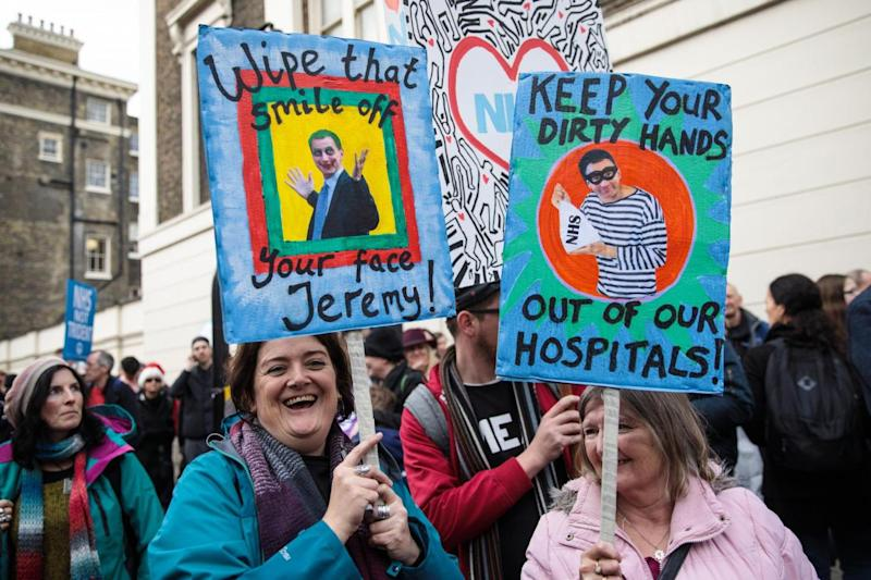 Activists hold up placards at the NHS march in central London (Getty Images)