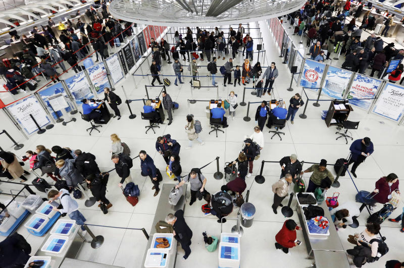 Travelers line up for a security checkpoint at John F. Kennedy International Airport, Wednesday, Nov. 21, 2018, in New York. The airline industry trade group Airlines for America expects that Wednesday will be the second busiest day of the holiday period behind only Sunday, when many travelers will be returning home after Thanksgiving. (AP Photo/Mark Lennihan)
