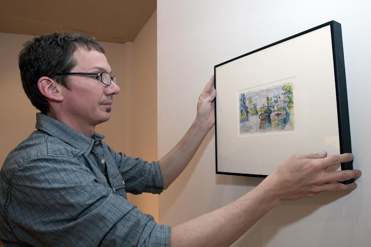"""Director of DAAP Galleries at the University of Cincinnati, Aaron Cowan hangs a piece of art by art forger Mark A. Landis, of Laurel, Miss. for a show called """"Faux Real"""" in Cincinnati, Ohio on Tuesday, March 27, 2012. The work of the convincing art forger who has spent nearly three decades copying artists like Picasso and donating his fake art to unsuspecting museums goes on display April Fool's Day. The University of Cincinnati exhibit will explore the problem of art forgery through a look at the unusual story of Landis. (AP Photo/Dottie Stover-University of Cincinnati)"""