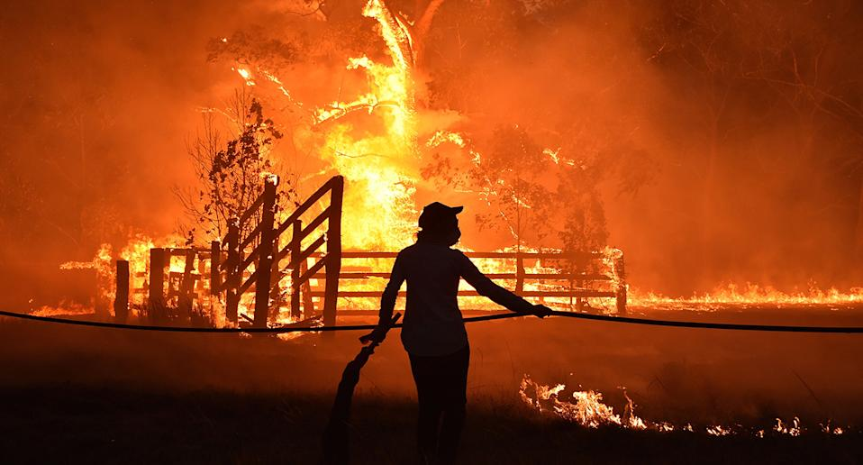 Residents defend a property from a bushfire at Hillsville near Taree, 350km north of Sydney. Source: Getty Images