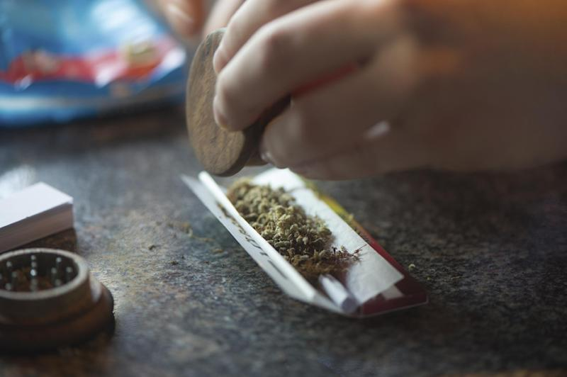 In this photo taken Friday, Dec. 20, 2013, a visitor rolls a marijuana joint in coffee shop Mississippi in Maastricht, southern Netherlands. While several U.S. states have moved to legalize the sale of marijuana, the Netherlands is going in the opposite direction, clamping down on its famed tolerance policy toward weed. In Maastricht, attempts to ban foreigners from buying weed have led to a resurgence of street-dealers, while Amsterdam is shutting marijuana cafes located too close to schools. (AP Photo/Ermindo Armino)