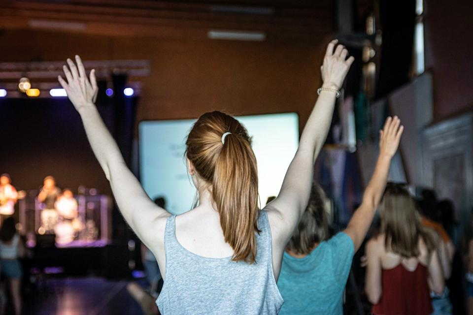 Young woman is worshipping at a service in a church