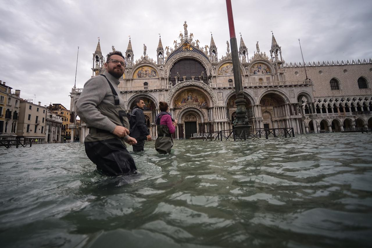 A general view shows people walking across the flooded St. Mark's Square, by St. Mark's Basilica on November 15, 2019 in Venice, two days after the city suffered its highest tide in 50 years. - Flood-hit Venice was bracing for another exceptional high tide on November 15, as Italy declared a state of emergency for the UNESCO city where perilous deluges have caused millions of euros worth of damage. (Photo by FILIPPO MONTEFORTE/AFP via Getty Images)