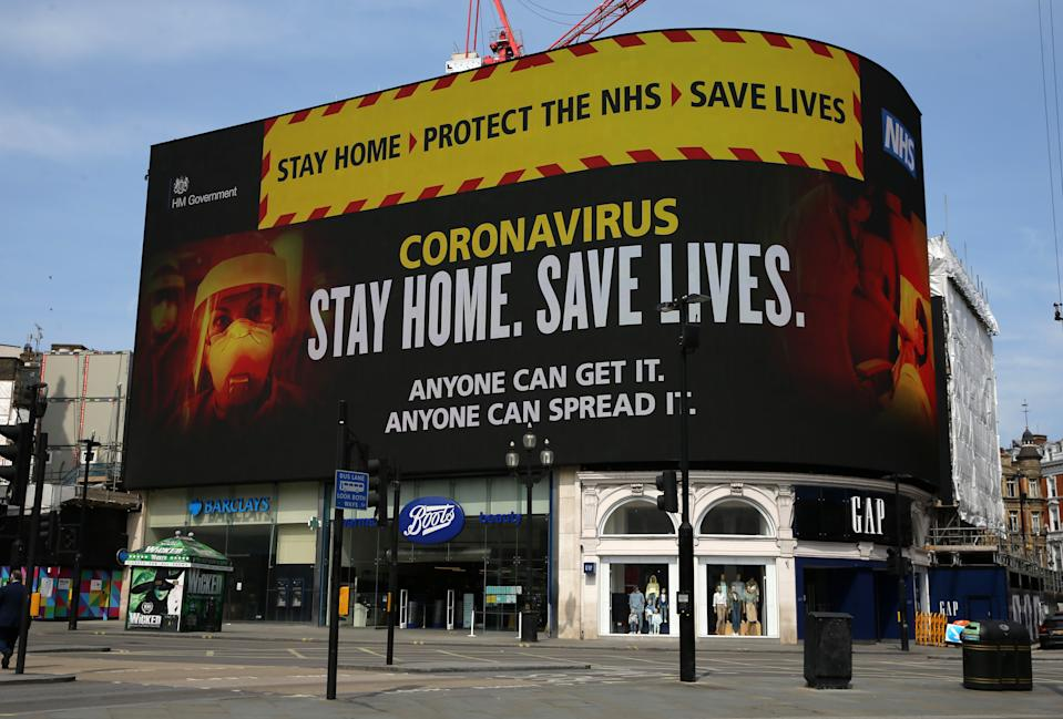 "LONDON, UNITED KINGDOM - APRIL 16: A NHS signage about coronavirus advice people to âStay home. Save lives"" is displayed on the advertising boards at Piccadilly Circus in London United Kingdom on April 16, 2020, as the government is to announce today a formal extension to the coronavirus lockdown that will last until at least May 7. (Photo by Isabel Infantes/Anadolu Agency via Getty Images)"