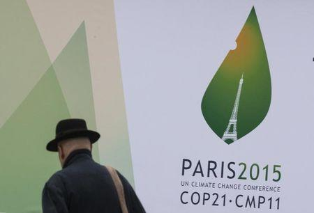 A passerby walks in front of posters for the forthcoming COP 21 World Climate Summit in Paris, France, November 2, 2015. REUTERS/Philippe Wojazer