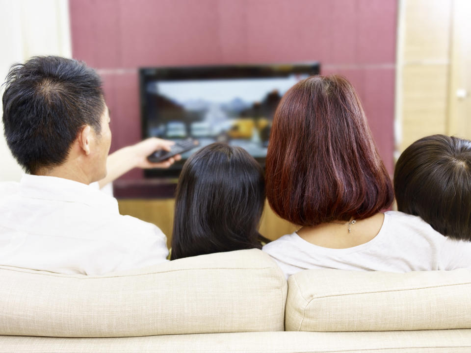 Family watching television from their living room couch.