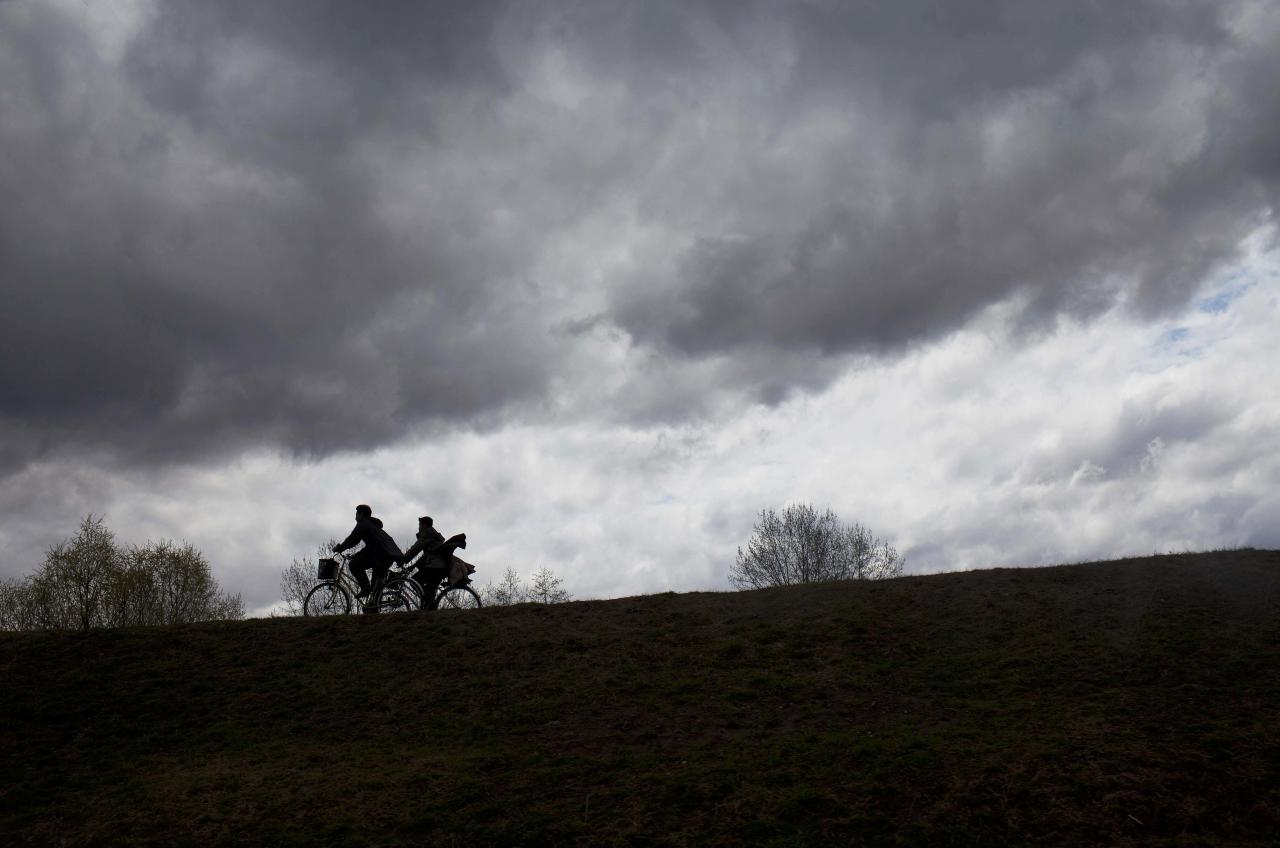 In this April 18, 2011 photo, men ride bicycles at the end of a work day in Pyongyang, North Korea. (AP Photo/David Guttenfelder)