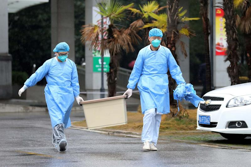 Medical staff carry a box as they walk at the Jinyintan hospital: Reuters