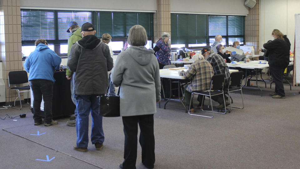 Voters line up to put their ballots in a ballot machine at the Soldotna Regional Sports Complex on Election Day, Tuesday, Nov. 3, 2020, in Soldotna, Alaska. (Ashlyn O'Hara/Peninsula Clarion via AP)