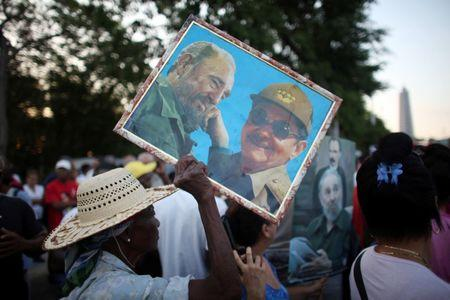 A woman carries a picture of Cuba's former President Fidel Castro (L) and Cuba's President Raul Castro during a May Day rally in Havana, Cuba, May 1, 2016. REUTERS/Alexandre Meneghini/Files