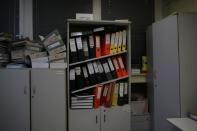 Folders are seen on a bookcase at a Greek Manpower Employment Organisation (OAED) office near Athens