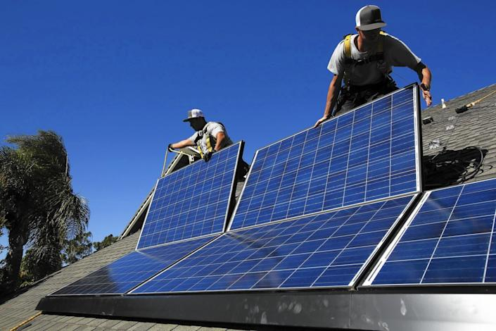 "Rogelio Mora, left, and Tyler Smith install solar panels on the roof of a home in Camarillo in 2013. <span class=""copyright"">(Anne Cusack / Los Angeles Times)</span>"