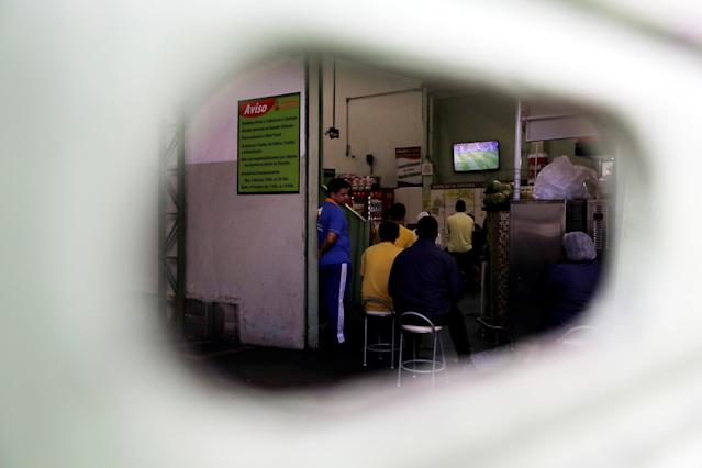 Workers watch the broadcast of the World Cup Group E soccer match between Brazil and Costa Rica inside a closed store in Sao Paulo, Brazil June 22, 2018. REUTERS/Paulo Whitaker