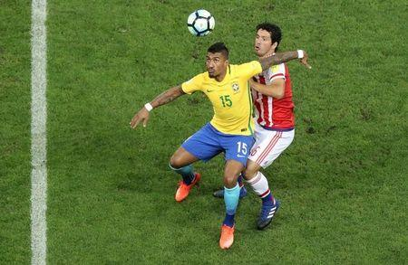 Brazil's Paulinho (15) and Paraguay's Cristian Riveros in action. REUTERS/Paulo Whitaker