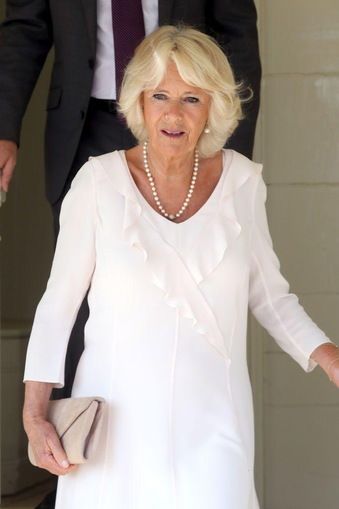 <p>While visiting the Isle of Wight and taking a stroll on Queen Victoria's private beach, the Duchess of Cornwall wore a cream colored ruffled dress with a timeless pearl necklace and a neutral clutch.</p>