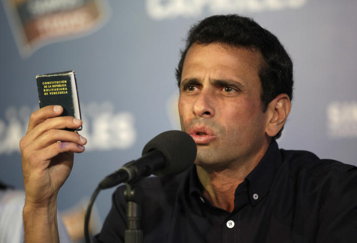 Opposition leader Henrique Capriles holds-up a copy of Venezuela's constitution during a press conference in Caracas, Venezuela, late Thursday, April 18, 2013. Venezuela's electoral council said Thursday it would audit the 46 percent vote that was not scrutinized election night. Capriles had demanded a full vote-by-vote recount, and has maintained that Sunday's election, which the National Electoral Council had declared won by Hugo Chavez's heir Nicolas Maduro by 262,00000 votes out of 14.9 million cast, was stolen from him through intimidation and other abuses.(AP Photo/Ariana Cubillos)