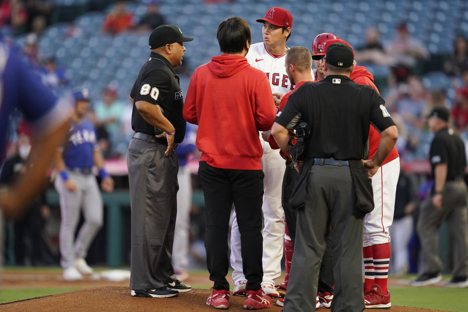 Los Angeles Angels starting pitcher Shohei Ohtani (17) is checked out on the mound after being hit by a sharp ground ball hit by Texas Rangers' Nathaniel Lowe during the first inning of a baseball game Friday, Sep. 3, 2021, in Anaheim, Calif. (AP Photo/Ashley Landis)