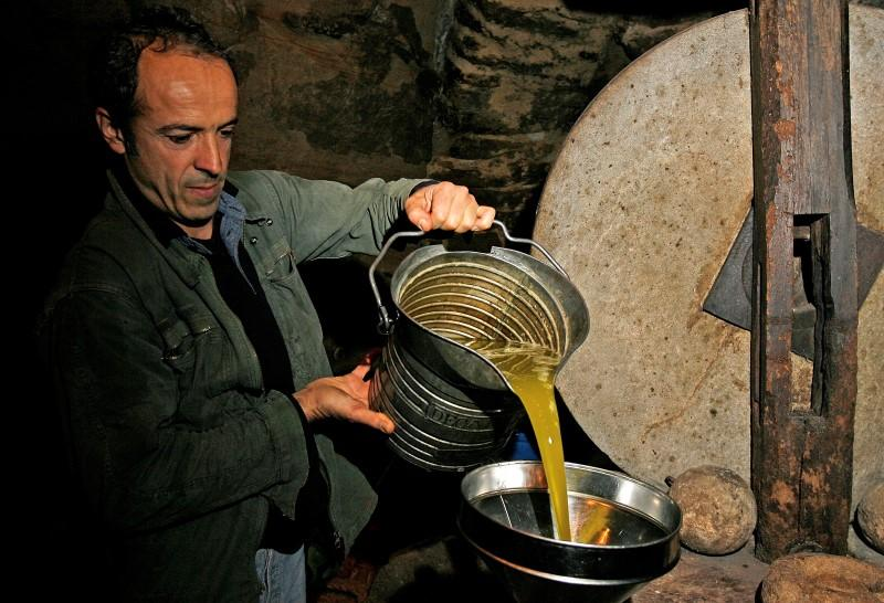"""An olive farmer fills up a vat with freshly extracted Verdale olive oil at the """"Moulin Fanouse"""" in Mirabel aux Barronnies in southern France"""