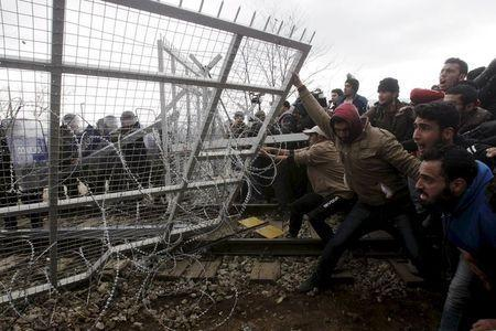 Stranded refugees and migrants try to bring down part of the border fence during a protest at the Greek-Macedonian border, near the Greek village of Idomeni, in this February 29, 2016 file photo. REUTERS/Alexandros Avramidis/Files