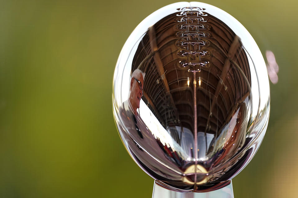 A man is reflected in the Lombardi Trophy at the NFL Experience Thursday, Feb. 4, 2021, in Tampa, Fla. The city is hosting Sunday's Super Bowl football game between the Tampa Bay Buccaneers and the Kansas City Chiefs. (AP Photo/Charlie Riedel)